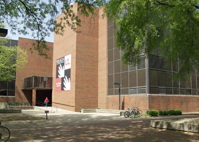 Strickler Hall with a bicycle rack and shade from the trees